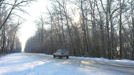 Two cars fast riding through snow covered icy road. Automobiles going at empty countryside route in winter forest on sunny day. Autos moving through scenic landscape way. Travel concept. Drone shot