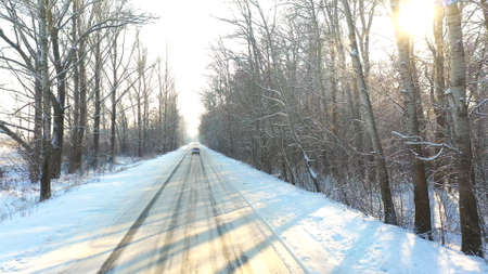 Following to white car riding through snow covered icy road. SUV driving at empty countryside route in forest on sunny winter day. Tracking the auto moving through scenic landscape way. Aerial shot