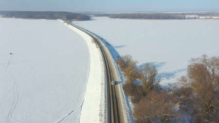 Aerial shot of car riding through snow covered road near frozen lake. White SUV driving at dam route on winter day. Flying over the auto moving through bridge of river. Scenic landscape way. Top view Imagens - 163735908
