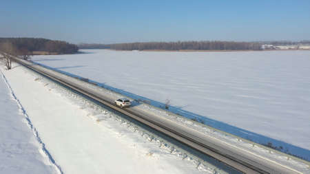 Aerial shot of car riding through snow covered road near frozen lake. White SUV driving at dam route on winter day. Flying over the auto moving through bridge of river. Scenic landscape way. Top view Imagens