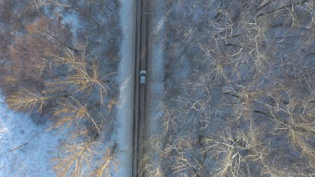 Above view of white SUV going on a snow covered forest road. Car rides at icy woods route at winter time. Auto driving over beautiful nature way. Concept of travel and active weekends. Aerial shot