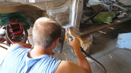 Unrecognizable repairer wearing protective mask welding some detail of auto. Mechanic working in garage or workshop. Man engaged servicing vehicles. Car repair and maintenance concept. Dolly shot