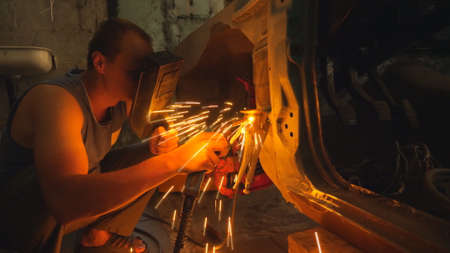 Repairer wearing protective mask welding some detail of auto. Mechanic working in garage or workshop. Man engaged servicing vehicles. Bright hot sparks flying around in dark. Car maintenance concept