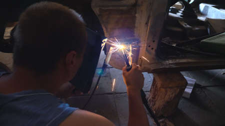 Repairer wearing protective mask welding some auto detail. Mechanic working at garage or workshop. Man engaged servicing vehicles. Bright sparks flying around in dark. Car repair concept. Slow motion