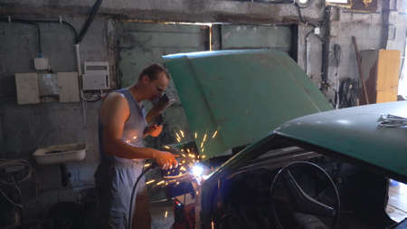 Professional repairer wearing protective mask welding auto details. Mechanic working in garage or workshop. Man engaged servicing vehicle. Hot sparks flying around. Car repair and maintenance concept Imagens