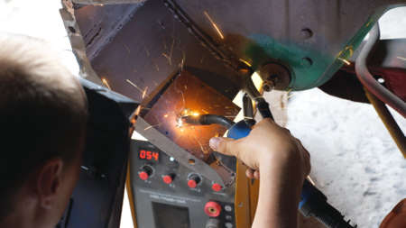 Professional repairer welding some auto detail. Mechanic using protective mask from sparks flying around. Man engaged servicing car in garage or workshop. Vehicle maintenance concept. Close up
