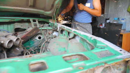 Professional repairer welding auto details. Skillful mechanic fixing automobile. Man engaged servicing car in garage or workshop. Vehicle repair and maintenance concept. Slow motion