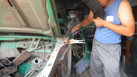 Professional repairer welding auto details using protective mask. Skillful mechanic fixing automobile. Man engaged servicing car in garage or workshop. Vehicle maintenance concept. Slow motion Imagens