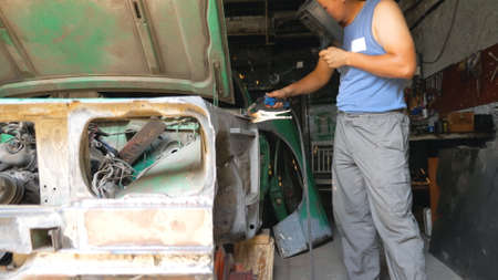 View of professional repairer welding auto details using protective mask. Skillful mechanic fixing automobile. Man engaged servicing car in garage or workshop. Vehicle maintenance concept