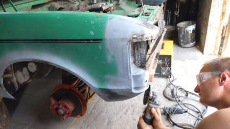 Mechanic polishing auto with electric equipment at workshop. Skillful mechanic restoring automobile. Repairman grinding old car body using grinder machine. Man engaged servicing car in garage. Slow mo