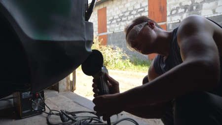 Mechanic wearing protective glasses polishing auto with electric tool in garage. Skillful mechanic restoring automobile. Guy grinding body of old car using grinder machine. Man engaged servicing car