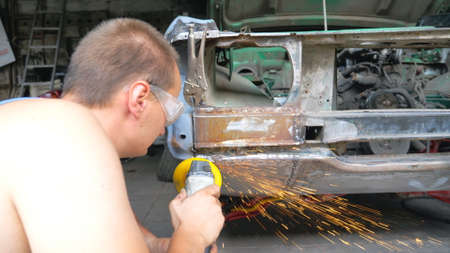 Mechanic polishing auto with electric tool at workshop. Skillful mechanic restoring automobile. Repairman grinding old car body using grinder machine. Man engaged servicing car in garage. Back view