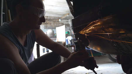 Mechanic polishing auto with electric tool at garage or workshop. Skillful mechanic restoring automobile. Bright sparks from polishing machine flying in dark garage. Repairman engaged servicing car Imagens