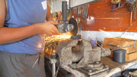 Professional mechanic processing metal detail with circular saw at workshop. Skillful repairer cutting metal using electric grinding wheel in garage. Bright hot sparks flying around. Slow motion Imagens - 163736067