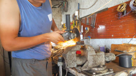 Professional mechanic processing metal detail with circular saw at workshop. Skillful repairer cutting metal using electric grinding wheel in garage. Bright sparks flying around. Slow motion Close up Imagens