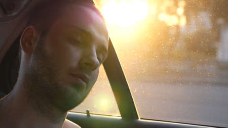 Young man sleeping inside moving car during long journey. Portrait of tired passenger traveling by car at summer evening. Road trip or summer vacation concept. Close up Slow motion