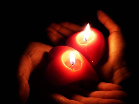 lurid: two open palms holding fired heart-shaped candles