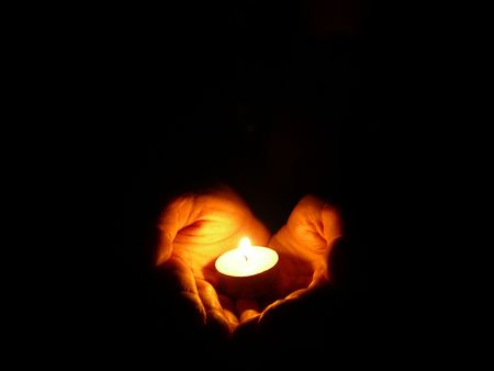 heart-shaped hands holding one candle in darkness Stock Photo - 781081