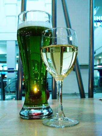 couple glasses of white wine and green beer in blue evening lighting Stock Photo