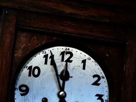 past midnight: face & hands of old wall clock in wooden clock-case