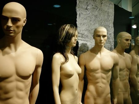 naked mannequins in dark shop window: one woman among men