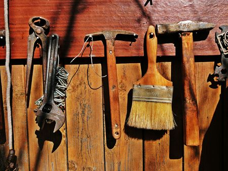 old tools, paint brush & hammers on wooden wall