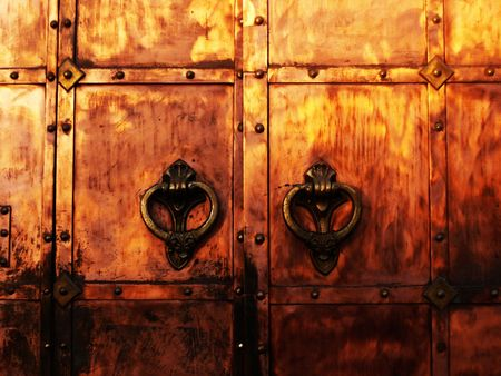 bronzy: medieval coopery gates with wrought knockers Stock Photo