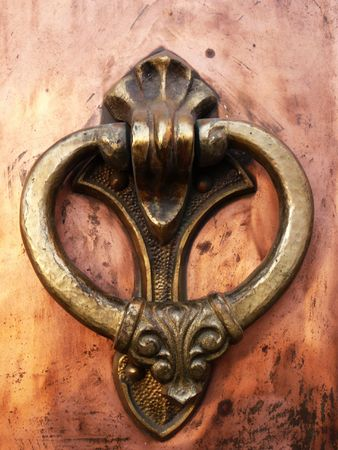 coppery wrought door knocker macro Stock Photo