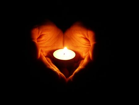 prayer candles: heart-shaped hands holding one candle in darkness Stock Photo