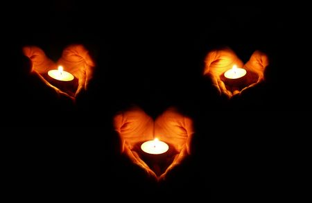 heart shape with hands: three couples of heart-shaped palms with candles on black background Stock Photo