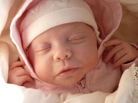 dreaming sweet baby girl in knitted bonnet and pink hood   Stock Photo - 3190762