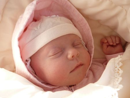 portrait sleeping newborn baby girl in knitted bonnet, wrapped soft blanket