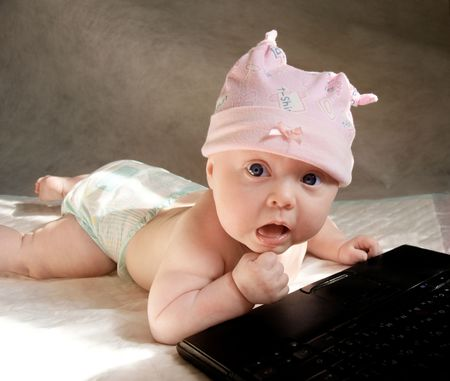 baby girl in funny pink bonnet playing with portable computer, her face with surprise expression