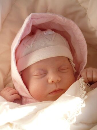 dreaming sweet baby girl in knitted bonnet and pink hood wrapped soft blanket  Banco de Imagens