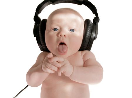 baby girl sings in big black headphones, on white background Stock Photo