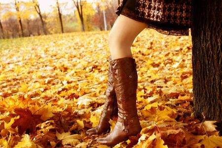 beautiful legs in hight leather boots among yellow maple leaves