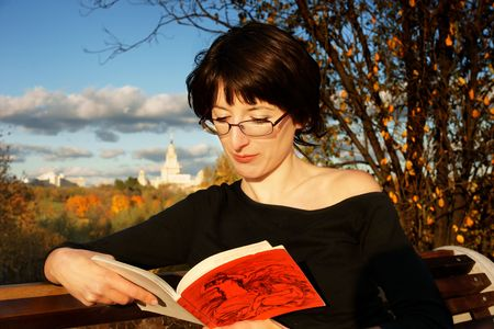 beautiful brunette in glasses reading book in autumn park, Moscow university behind photo