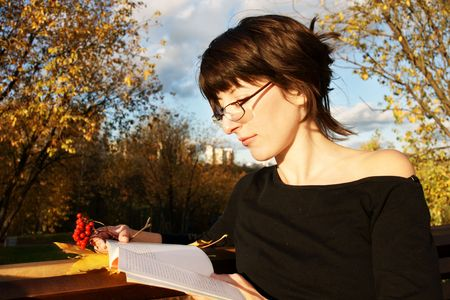 beautiful brunette in glasses reading book in autumn park