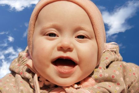baby girl is delighted with something, looks in camera photo