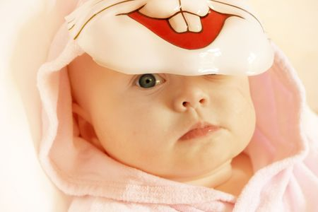 unmask: sad baby girl under a mask of pink rabbit
