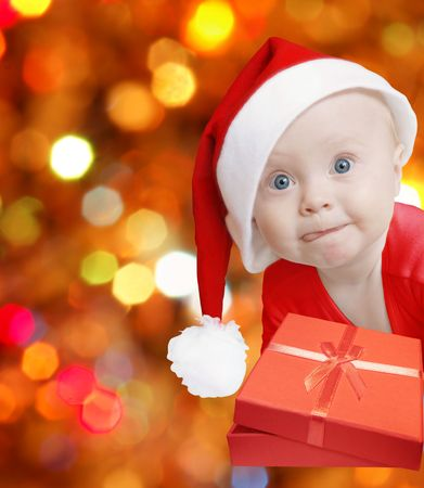 funny baby in Santa hat with present box on bright festive background, space for text