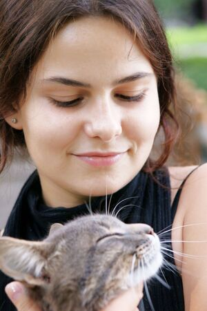 young beautiful dark-haired girl with tabby cat