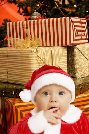 baby in Santa uniform in utter surprise, a lot of present boxes behinde photo