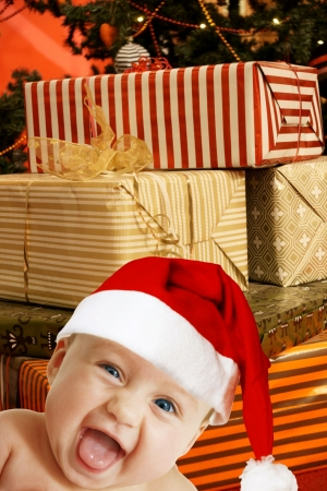 funny baby in Santa hat, several present boxes behind photo
