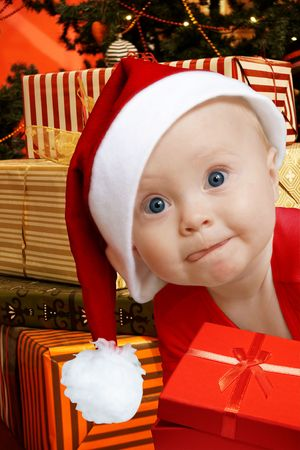 baby in Santa uniform in utter surprise, a lot of present boxes behind Stock Photo - 4001154