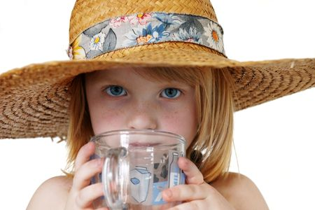 cute redhead girl 4 years old covered with big broad-brim straw hat drinking a cup of water, isolated on white