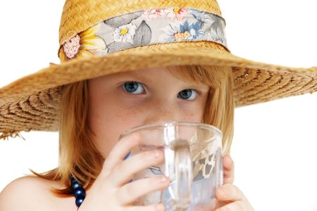 cute redhead girl 4 years old covered with big broad-brim straw hat drinking a cup of water