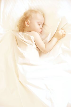 a sweet little child sleeping on a white bed sheets, space for text photo