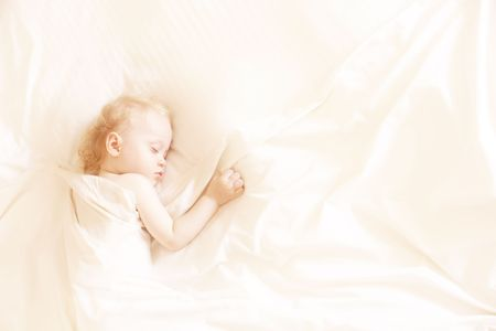 a sweet little child sleeping on a white bed sheets, space for text