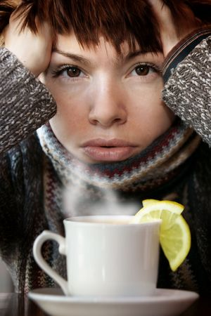 young beautiful woman in knitted scarf, with the cup of hot tea Banco de Imagens